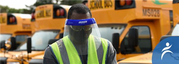 Bus driver wearing a mask and face shield, standing in front of buses.
