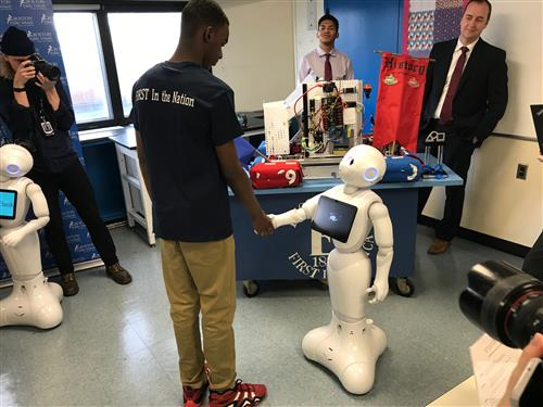 Pepper shakes hands with a student