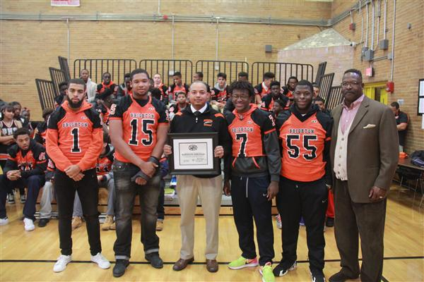 Brighton High School head coach Randolph Abraham stands with his players and his award.