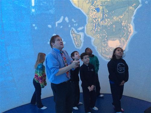 Vernon Domingo of Bridgewater State University inside an inflatable Peters Projection globe with BPS students.
