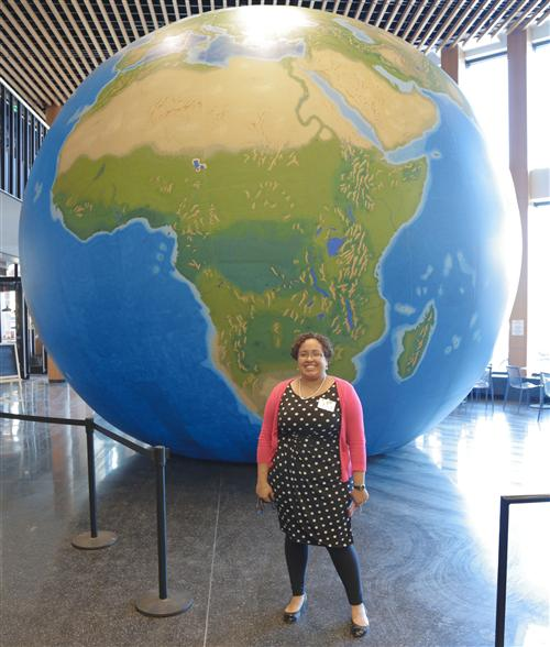 Social Studies director Natacha Scott in front of a Peters Projection globe.
